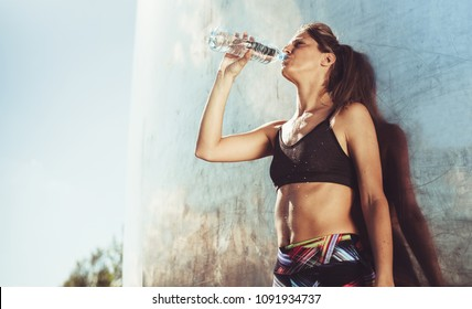 Young woman with fit body taking a break after intensive exercise. Female taking a rest after exercising outdoors.