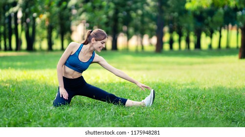 Young woman in fit wear doing stretching exercise, before morning jogging or workout, outdoors. Fitness, sport, exercising and workout in city concept. Copy space empty area for some text or slogan.