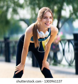 Young woman in fit wear and headphones tired, during morning jogging outdoors, with smile. Fitness, sport, exercising and workout in city concept.
