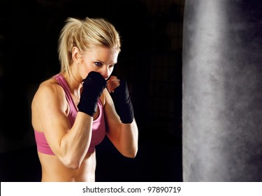 Young woman fitness boxing in front of punching bag. Isolated on black.
