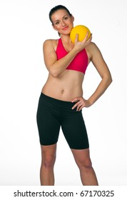 young woman in fitness clothes with yellow ball