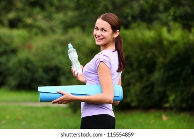 Young  woman with fitness mat and bottle of fresh water in the park