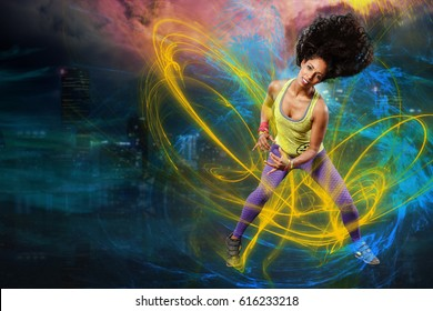 young woman at fitness or zumba dancing in front of fireworks