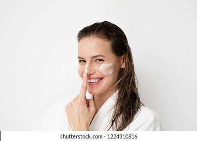Young woman with flawless skin, applying moisturizing cream on her face. Playing with cream and making lines on her face. Photo of woman after bath in white bathrobe  white . Skin care concept