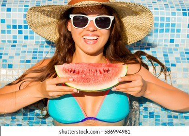 Young woman floating in the blue pool. Tropical fruit diet. Summer holiday idyllic.