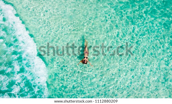 Young woman floating in the clear sea of the Mexican Caribbean. Cancun, Mexico.