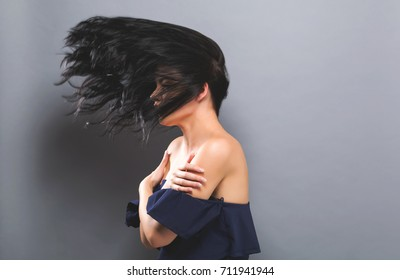 Young woman with floating hair on a solid background