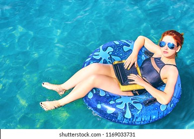 Young woman is floating on the sea in a swimming circle. Femaie is relaxing on the sea on the inflatable ring with minicomputer. View from above