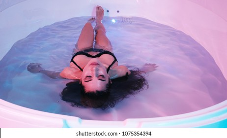 Young woman floating in Spa bath or swimming pool, she is very relaxed. Welness concept.