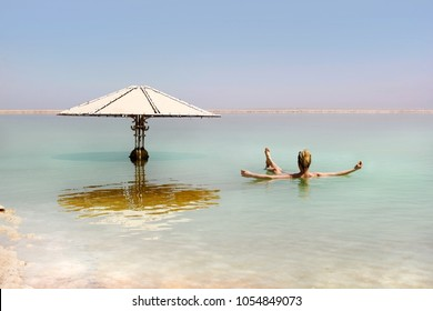 young woman floating in the waters of the Dead Sea in Israel