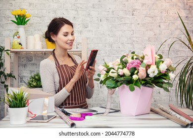 Young woman florist at work. Business woman sale and floristry concept happy smiling woman making bunch at flower shop. Beautiful girl florist with flowers. Female florist working in from home
