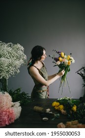 Young woman florist working in her flower studio, making beautiful bouquet using fresh plants and flowers. Small business.