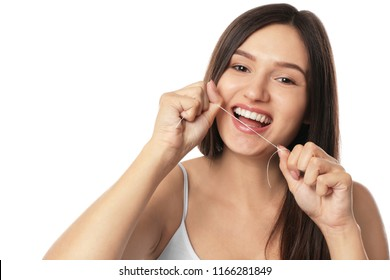 Young woman flossing her teeth on white background