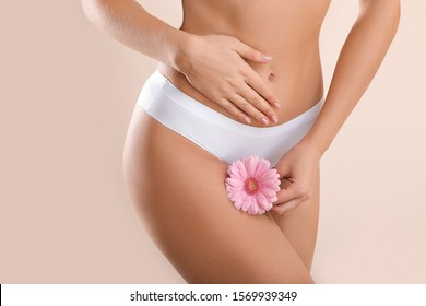 Young woman with flower on light background. Gynecology concept