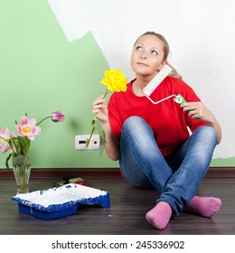 Young woman with flower and paint roller in hands painting interior wall of home