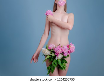 Young woman with flower showing smooth skin after bikini epilation. Naked beautiful woman with perfect body and shiny skin holding pink rose. Flowers on the vagina instead of clothes