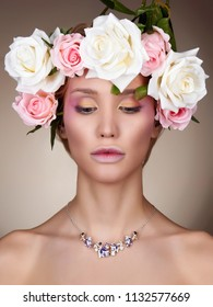 Young woman with flowers in Hair. Beautiful Girl with Rose flowers on her head. Professional make-up
