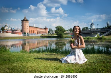 Young woman with flowers in light dress sits on the grass on background of kremlin and church in a small town in Russia. Beautiful romantic girl on the riverbank is looking to the sky