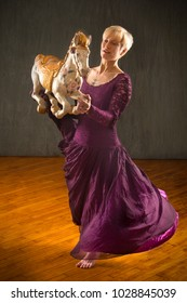 Young woman in flowing, vintage purple dress, dancing with an antique carousel horse in the studio.
