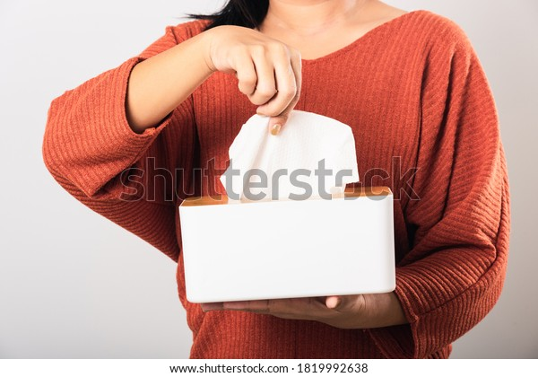 Young woman flu she using hand taking pulling white facial tissue out of from a white box for clean handkerchief, studio shot isolated on white background, Healthcare medicine concept