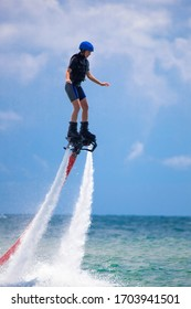 Young woman is flying at the aquatic flyboard. Water extreme spo