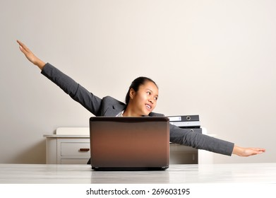 Young woman flying behind her laptop while sitting at her desk.