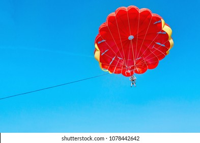 Young woman is flying on a red parasailing on a background of blue sky
