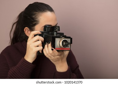 Young woman focusing on the viewer with a vintage camera