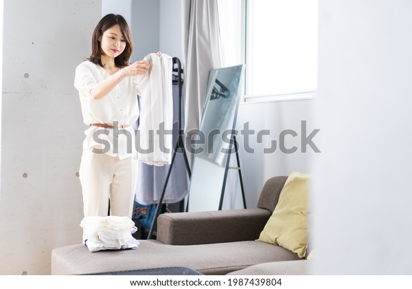 A young woman folding laundry at home