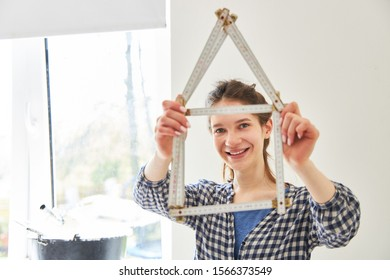 Young woman with folding rule house as a symbol of home construction and home renovation