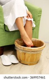 Young woman in foot-bath in oriental herb water for body detox