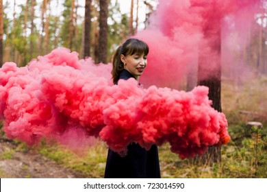 Young woman in forest having fun with red smoke grenade, bomb