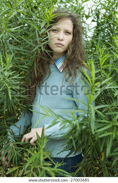 Young woman in forest. looking through the leaves
