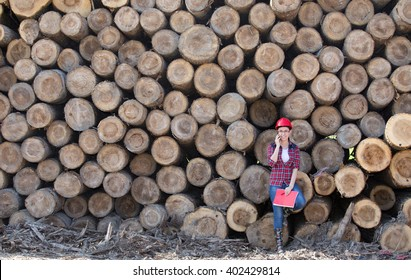 Young woman forestry engineer standing in front of wooden trunks and talking on phone