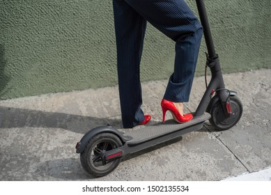 Young woman in formal wear on red hight heels is standing on electrical scooter. Close-up of female legs. A business woman in a trouser suit and red shoes moves around the city on an electric scooter.