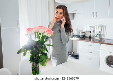Young woman found bouquet of roses talking on phone on kitchen. Happy excited girl smiling