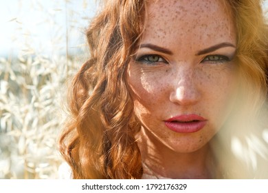 Young woman with freckles. Beautiful Red-haired young woman walks in  wheat field at summer time.
