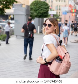 Young woman with freckles in casual outfit and backpack walking on european city streets alone. Summer day. Copy space