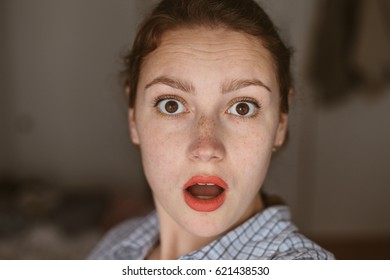 Young woman with freckles is surprised, beauty portrait with red lips