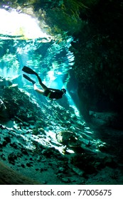 A young woman free dives into a Cenote