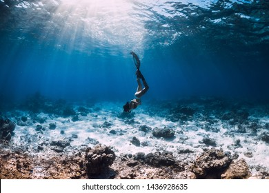 Young woman freediver glides over sandy sea with fins in blue ocean.