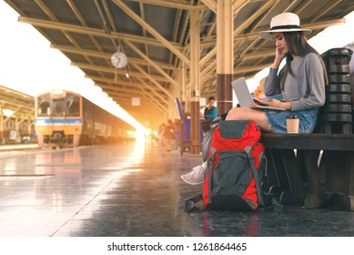 Young woman  freelance working laptop and using mobile for searching location at train station before travel, Summer travel,hipster travel are Waiting for the train at the platform of railway station.