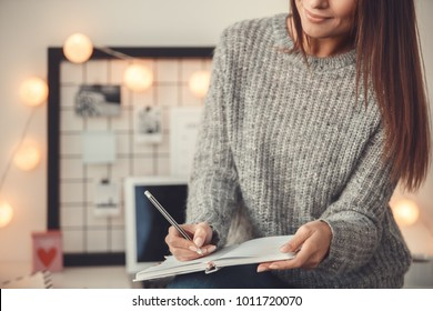 Young woman freelancer indoors home office concept winter atmosphere taking notes in planner close-up