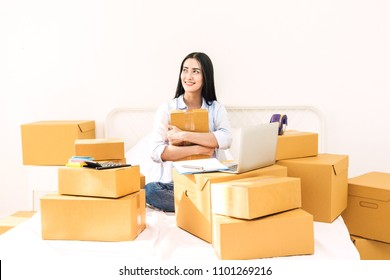 Young woman freelancer working and holding cardboard box on bed at home - SME business online and delivery concept