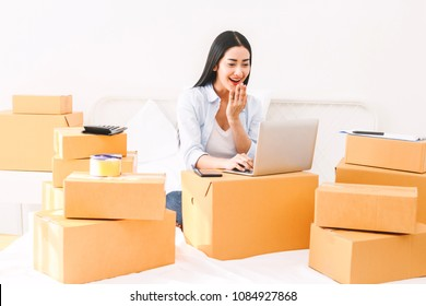 Young woman freelancer working and use laptop computer with cardboard box on bed at home - SME business online and delivery concept