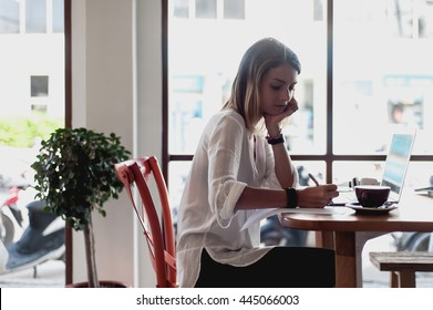 Young woman freelancer writing notes in cafe