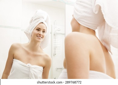 Young Woman Fresh From Shower, Wrapped with White Towels, Looking Herself at the Mirror In the Bathroom While Touching her Face.