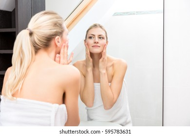 Young Woman Fresh From Shower, Wrapped with White Towels, Looking Herself at the Mirror In the Bathroom While Touching her Face
