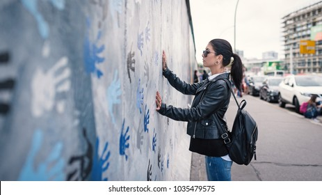 Young woman in front of Berlin Wall.