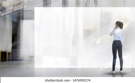 Young woman in front of big white banner in the open exhibition or industrial space. Space for your image or text. Business and strategy concept